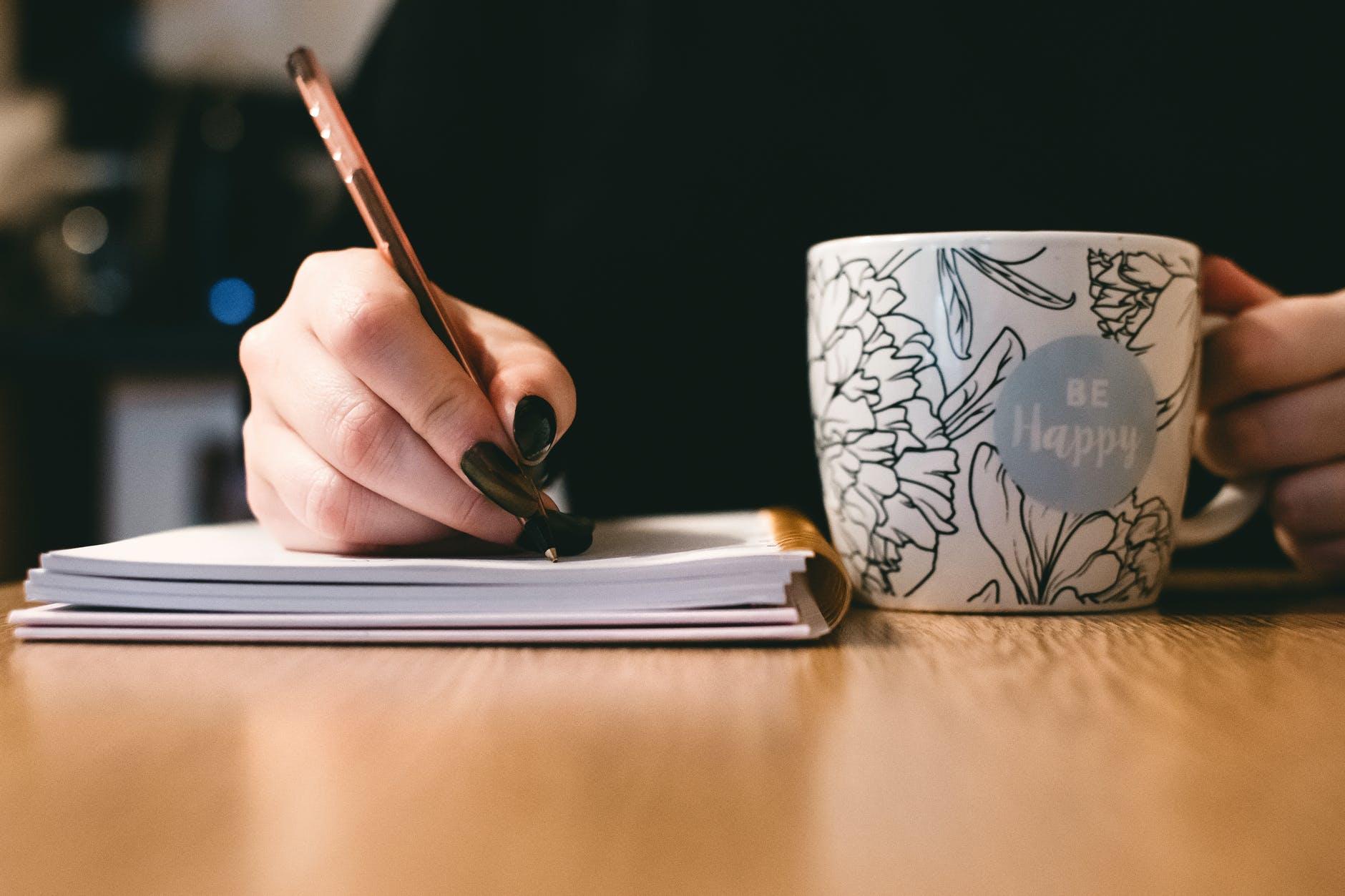 main écrire tasse